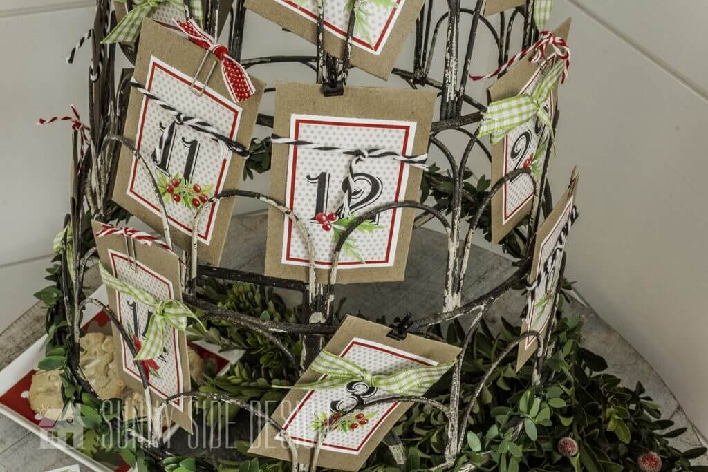 Service Christmas countdown. Kraft coin envelopes with service activities tucked inside are placed on a wire Christmas Tree card holder.
