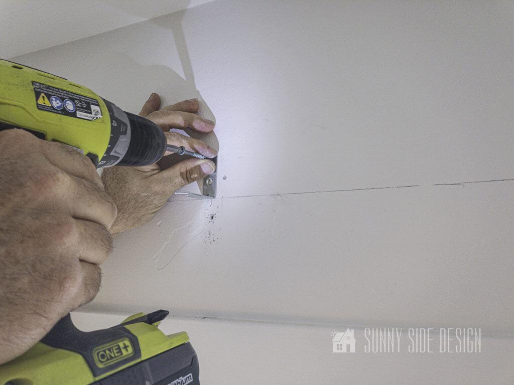 Secure angle iron bracket to wall