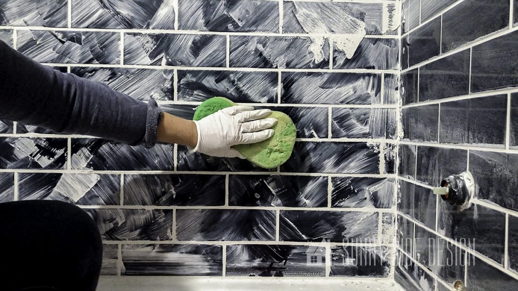 wiping grout with wet sponge