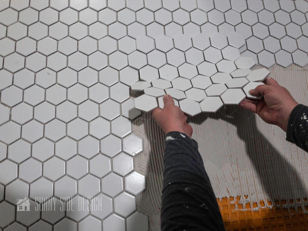 line hexagon floor tile with other tiles and slowly slide it into position