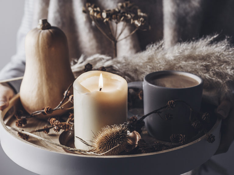 Cozy fall decor ideas for home. Woman holding tray with lit candle, pumpkin, hot cocoa and dried flowers.