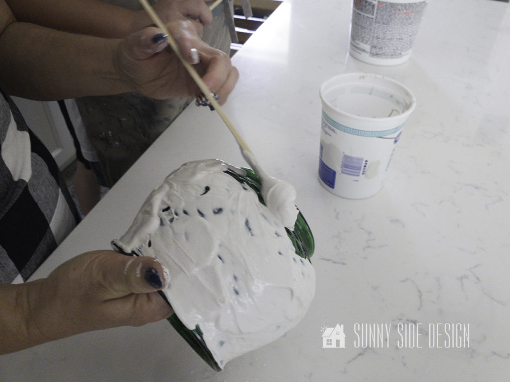 Woman's hands preading plaster mixture on green glass vase for DIY decor for home.