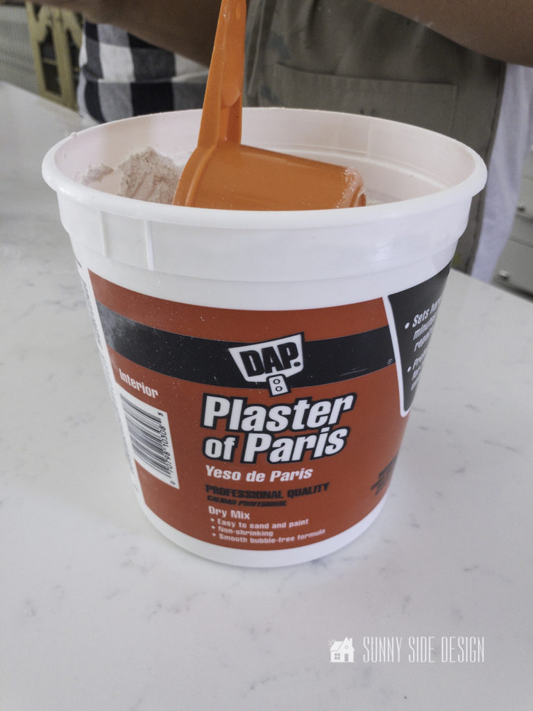 Tub of Plaster of Paris with a measuring cup.