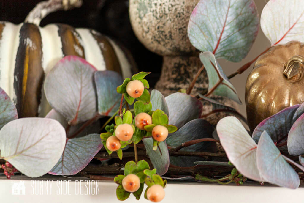 Cozy Fall Home Decor, eucalyptus, fall berries, candles and pumpkins placed on a fireplace mantle.