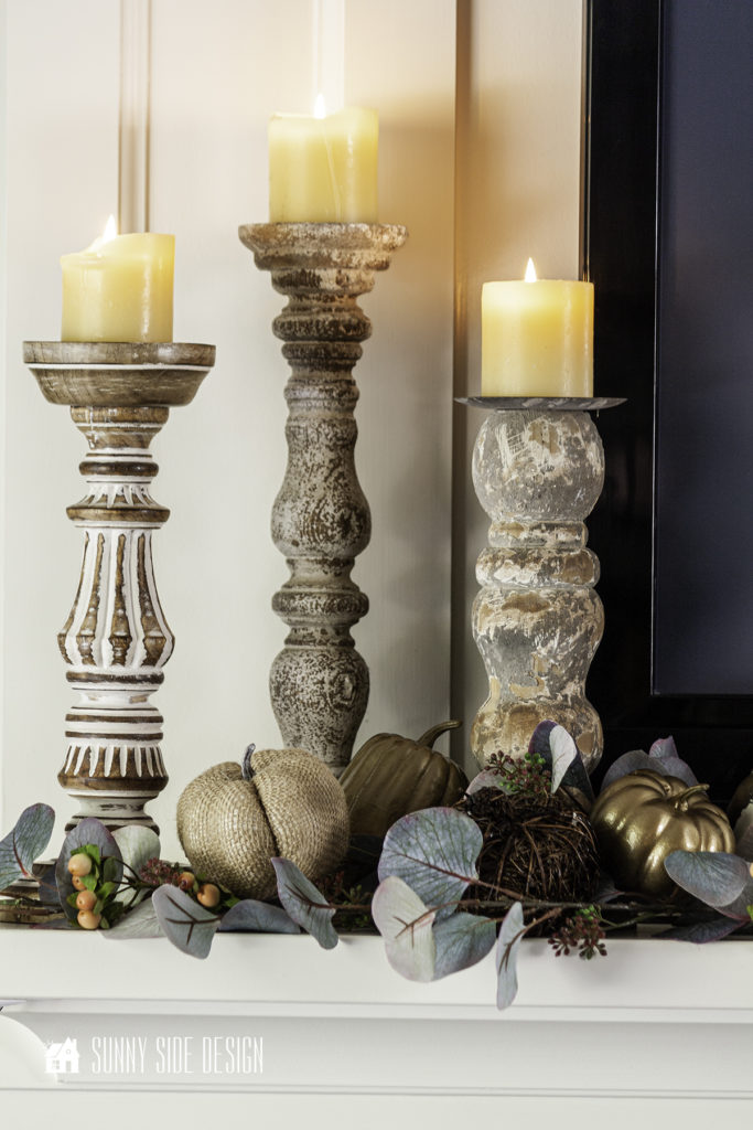 Cozy Fall Decor Ideas for Home. Three rustic wood candlesticks with glowing candles on a mantle. Eucalyptus, berries and pumpkins fill in around candlesticks.