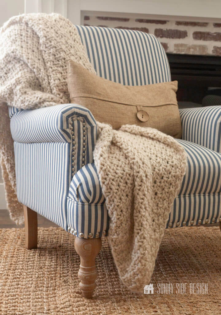 Cozy Fall Home Decor Ideas. Blue and white striped chair with a chunky natural knit throw, in front of the fireplace