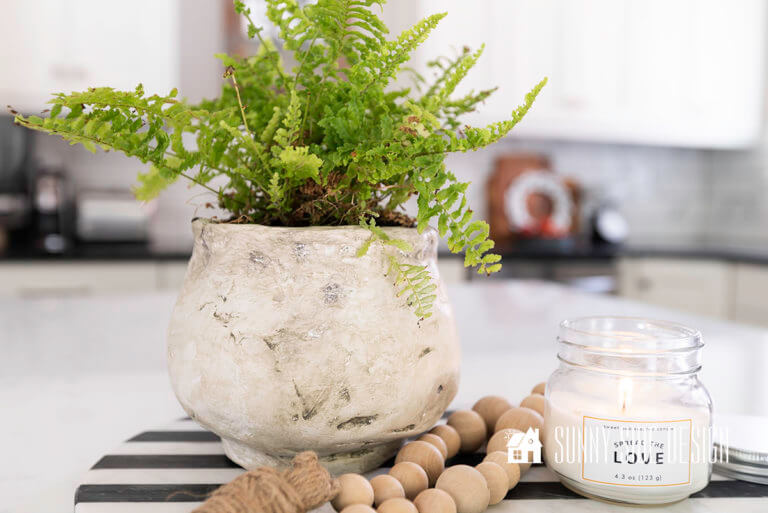 DIY textured pot with fern styled on a black and white tray with boho beads and a lit jar candle.
