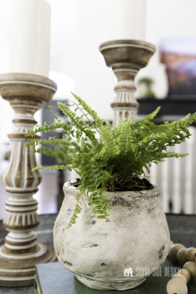 DIY textured pot styled on a galvanized tray with two wod candlesticks and boho beads.