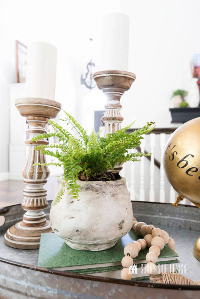 DIY Texture pot with a fern plant styled on a galvanized tray with two candlesticks, boho beads and a globe.