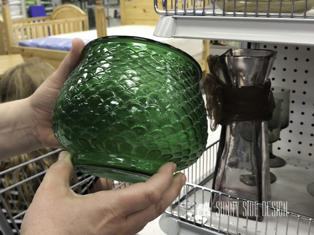 Woman holding a green glass vase at the thrift store.