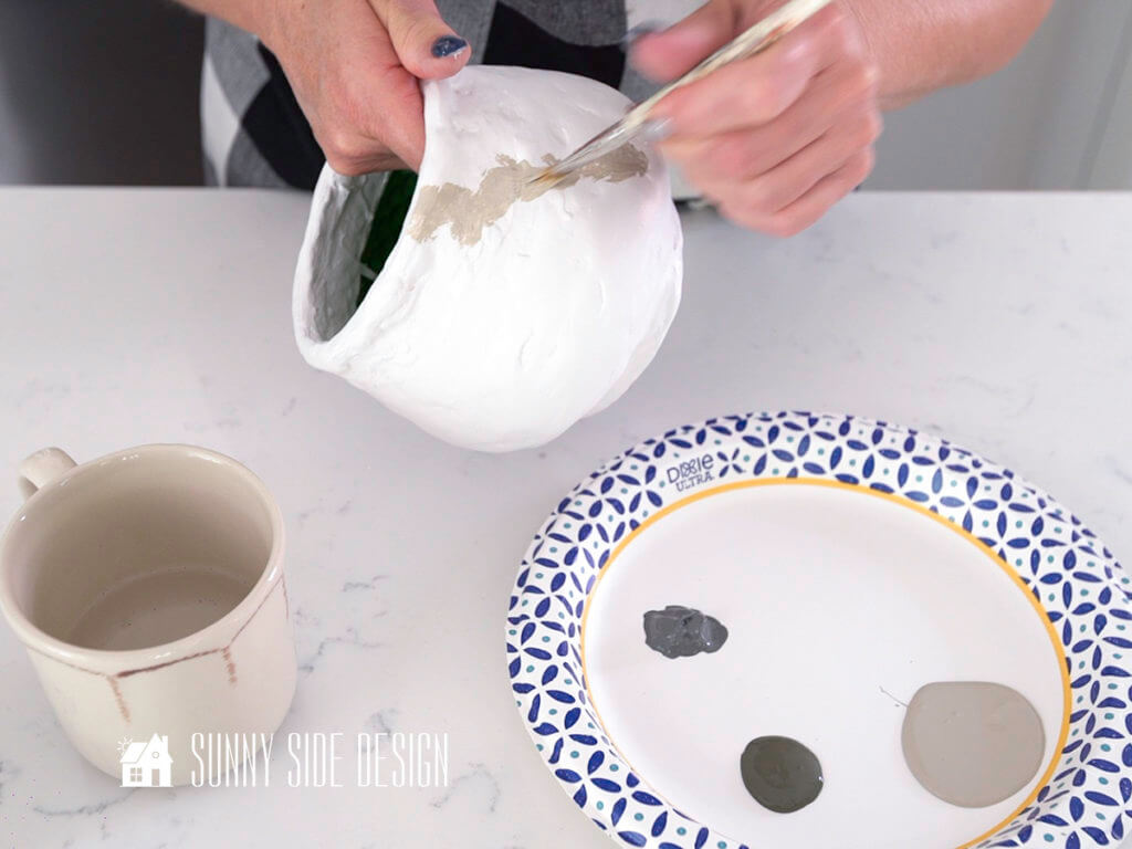 Woman's hands applying light grey paint for add shading and texture to plaster pot.
