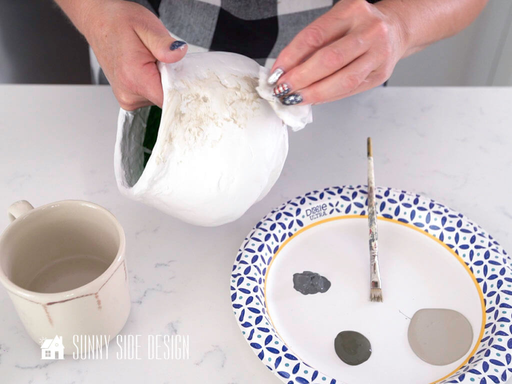 Woman's hands holding textured pot blotting and blending paint for DIY decor for home.
