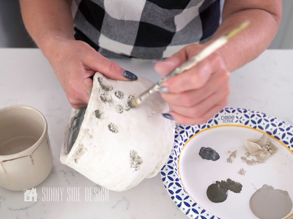 Woman's hands dabbing on darker grey paint, focusing on dimples and crevices on the pot surface. Creating DIY decor for home.