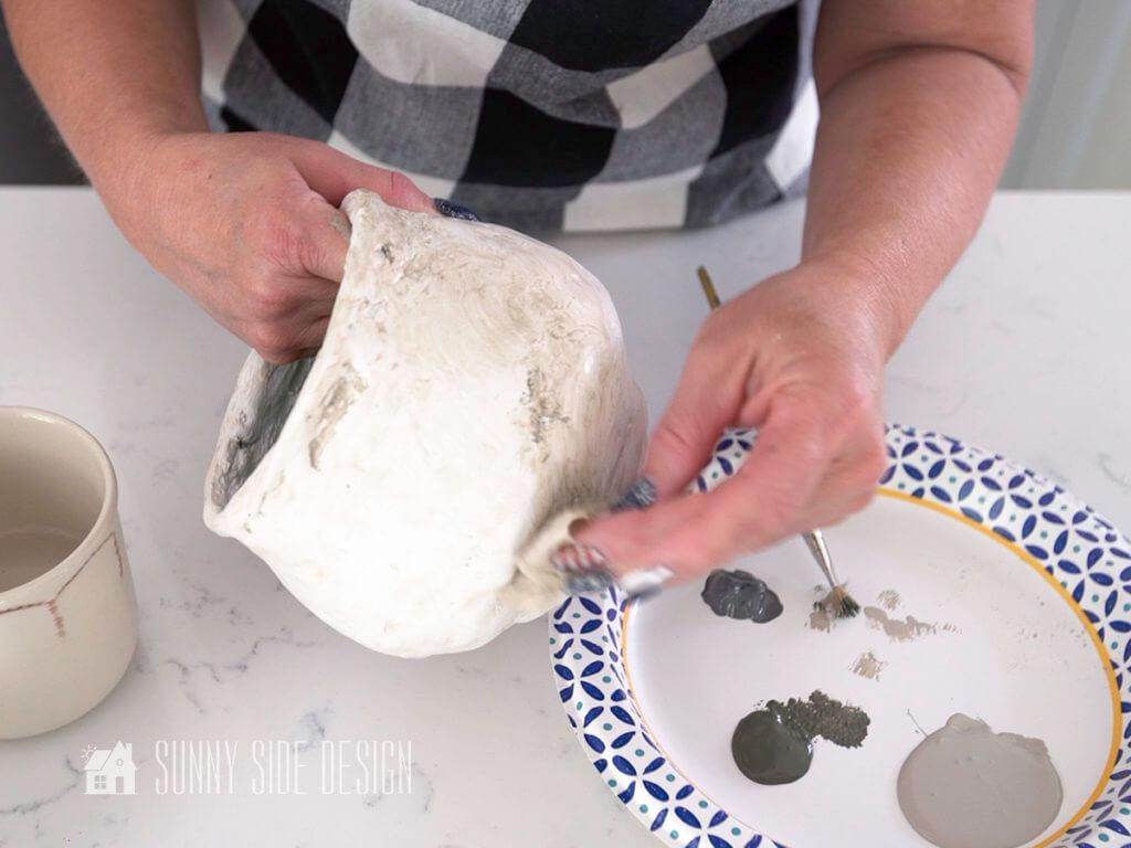Woman's hands holding textured pot, blotting and blending paint.