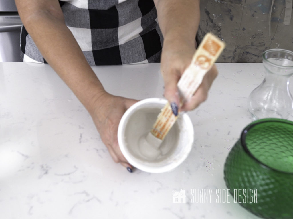 Woman's hands stirring Plaster of Paris for DIY decor for home. Plaster now thick enough to hold it's shape.
