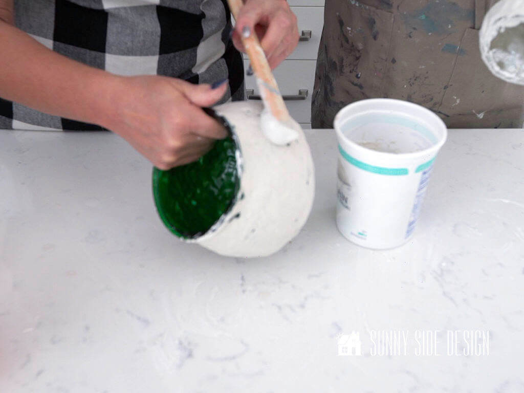 Woman's hands spreading second coat of Plaster of Paris on pot creating DIY decor for home.