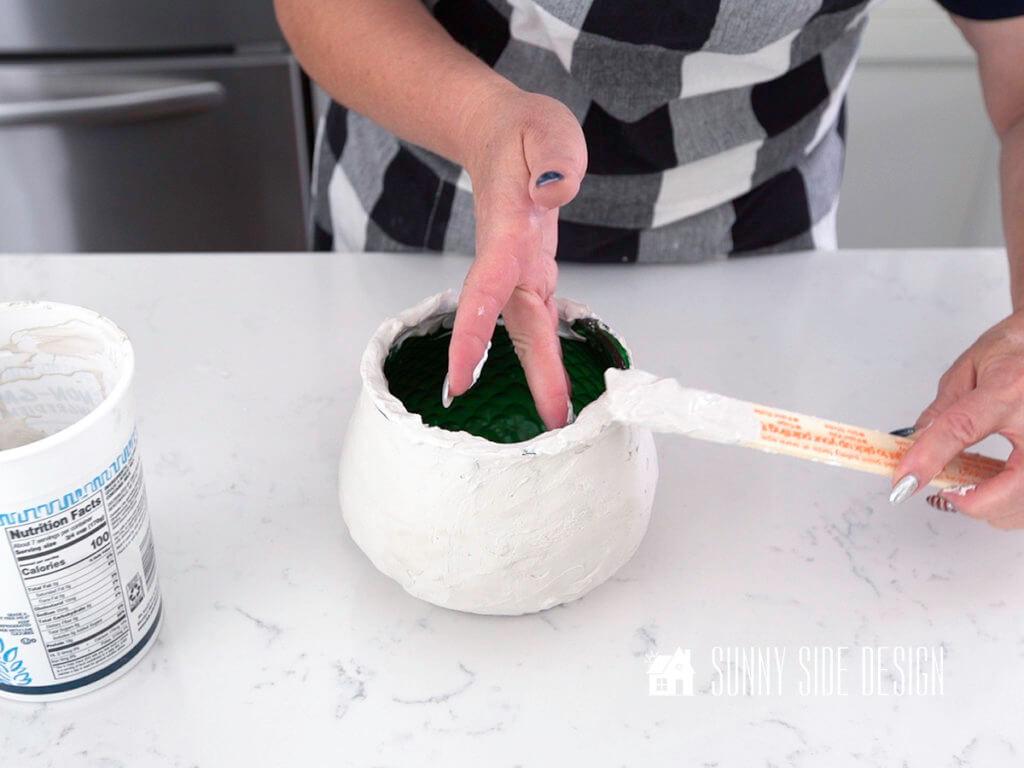 Woman's hands spreading plaster on rim of vase for DIY decor for home.
