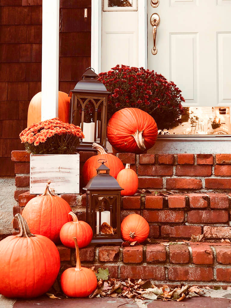 Brick stairs & front porch with pumpkins, mums and lanterns.