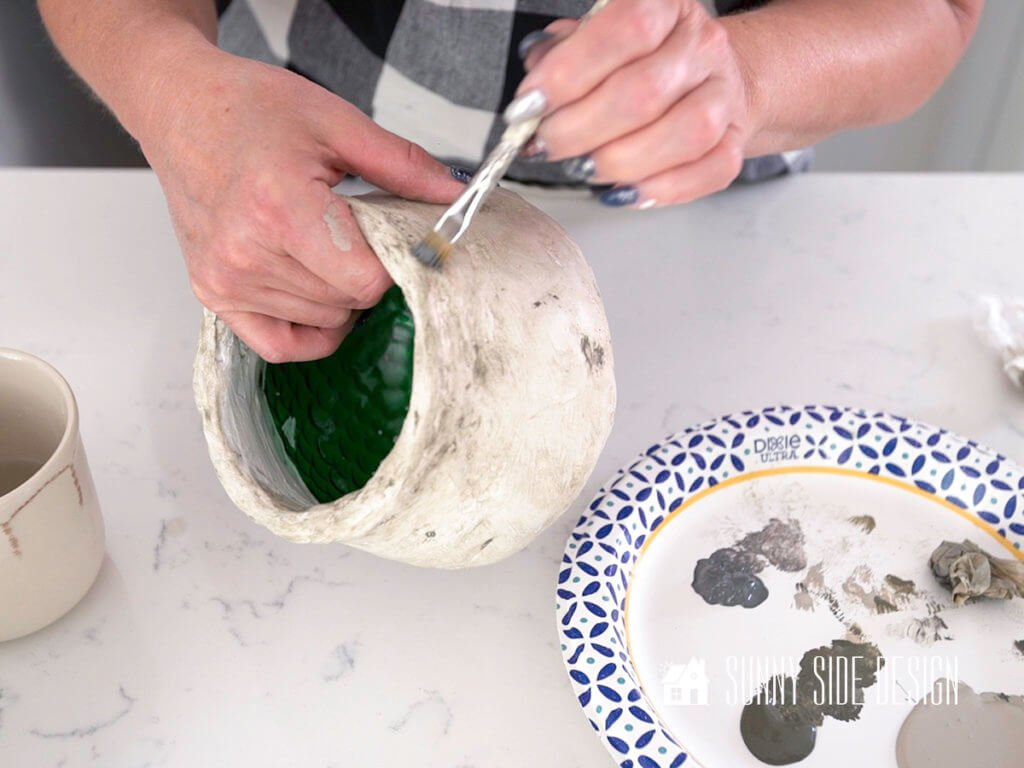 Woman's hands dabbing on a darker grey paint on textured plaster pot. Creaing DIY decor for home.