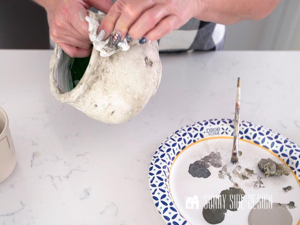 Woman's hands holding textured pot, blotting paint.