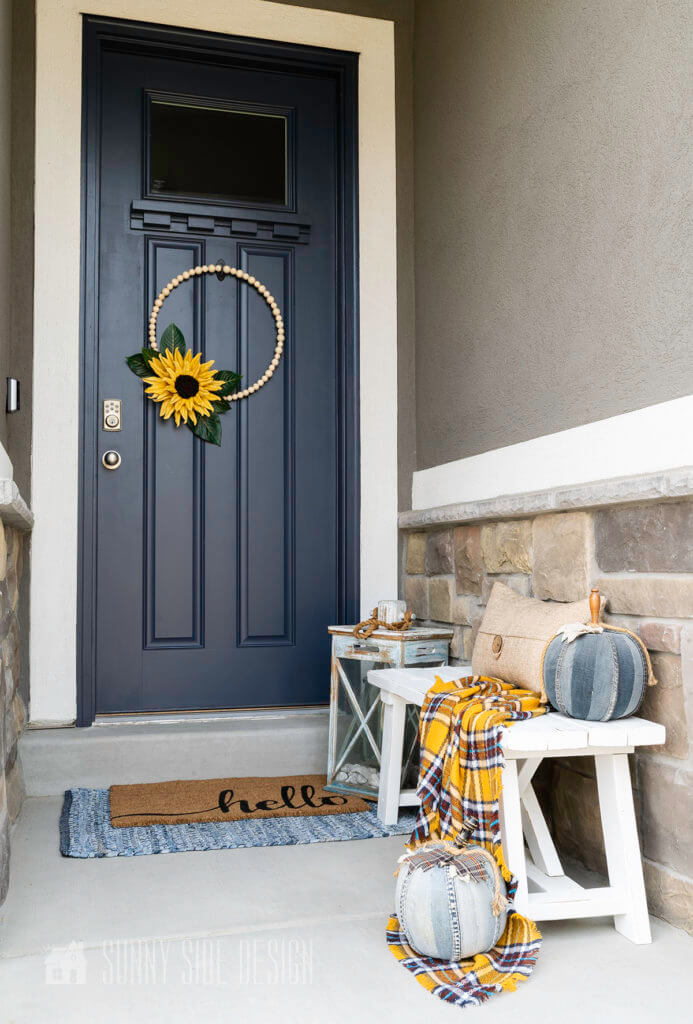 Fall DIY decorating ideas on the front porch. Modern bead and sunflower wreath on a navy blue door. Hello door mat is layers with a denim rug. White wood bench is topped with a yellow plaid throw blanket with a natural colored pillow and 2 denim pumpkins. A Rustick blue lantern is placed near the front door.