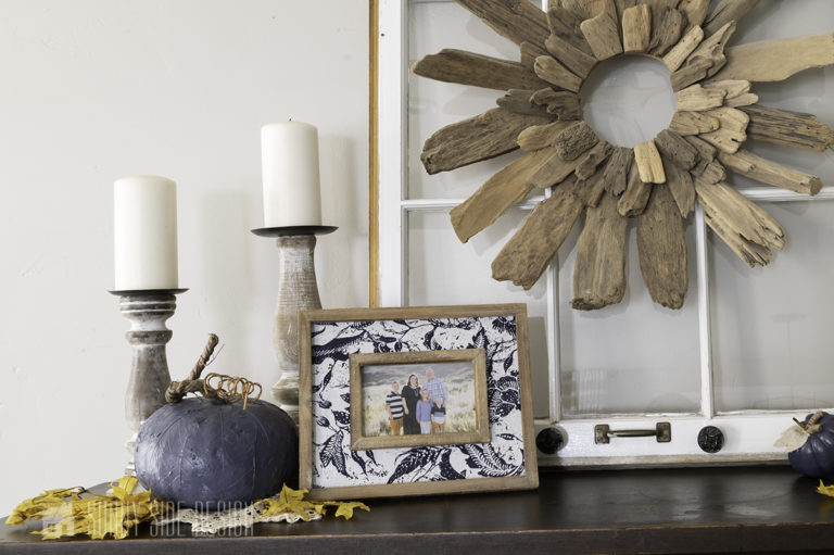 Easy fall DIY decorating idea with rustic candlesticks, pumpkin and family photos with maple leaves scattered around.