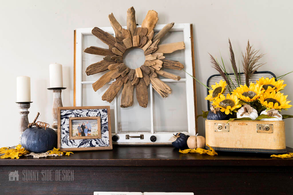 cheap fall DIY decorating ideas on top of the piano. Center is an old pane window on which a drift wood wreath is hanging. On the left there are 2 rustick candlesticks, a navy blue pumpkin, family photos and yellow maple leaves. On the right is a sunflower floral arrangement with pampas grass and mini pumpkins places in a vintage suitcase. Mini pumpkins and leaves anchor this arrangements.