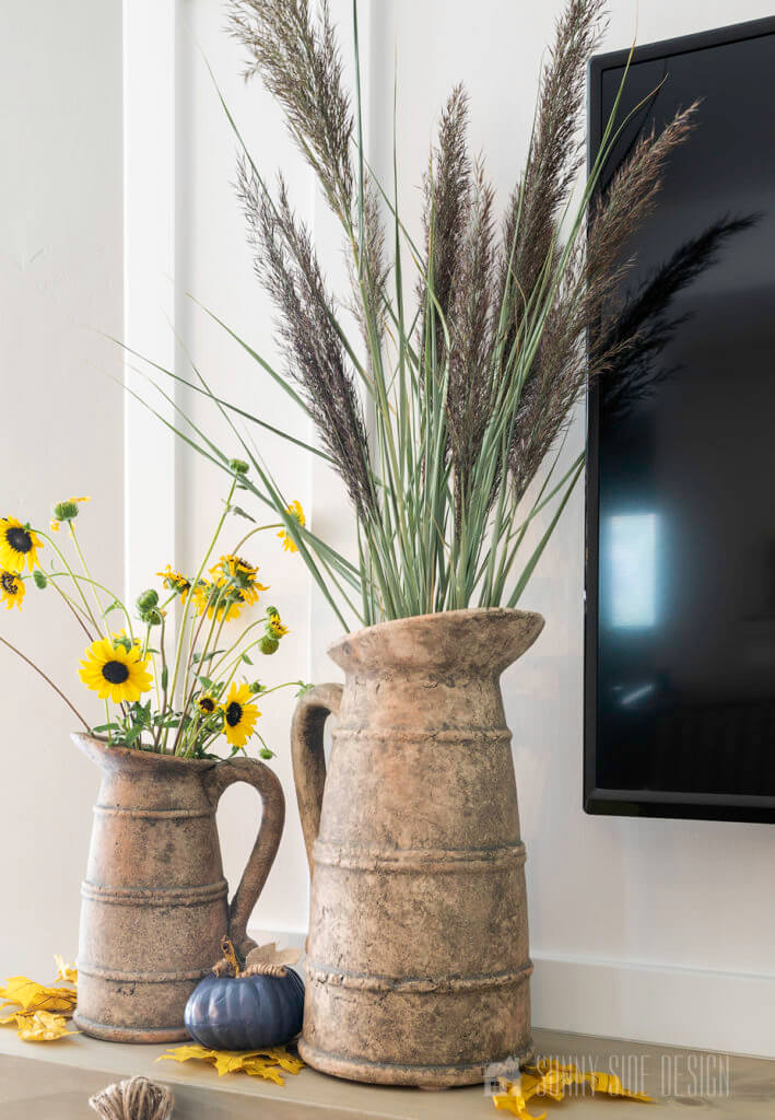 Rustic pitchers filled with fall foliage, fresh sunflowers and pampas grass for easy fall DIY decorating ideas.