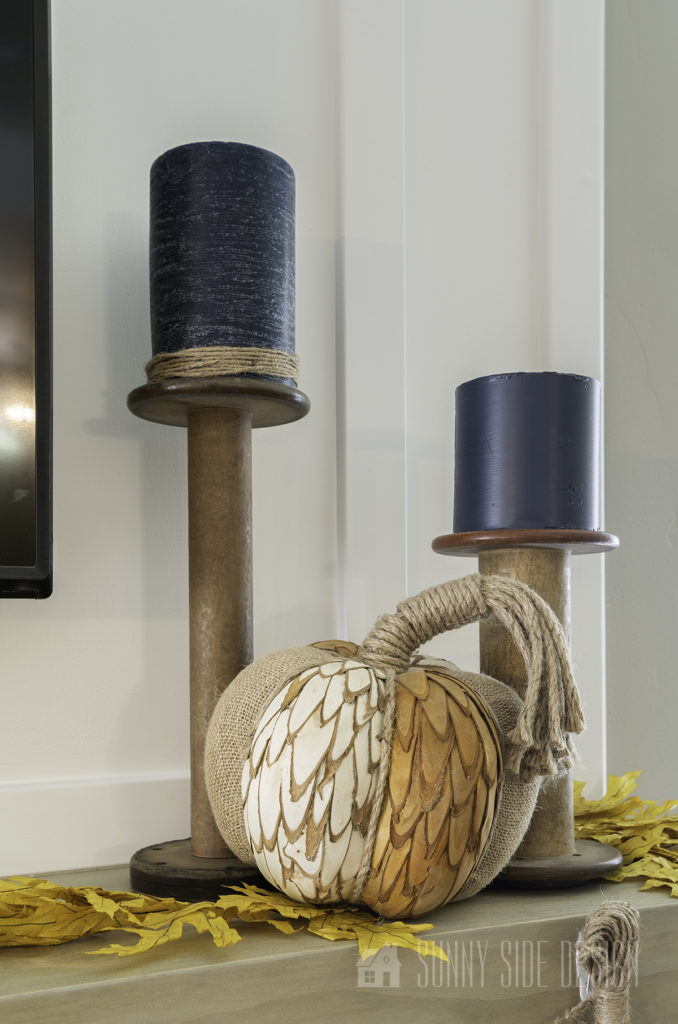Large old wooden spools are placed on the mantle with navy blue candles. A pumpkin is placed in front of them and yellow maple leaves are sprinkles around the mantle.