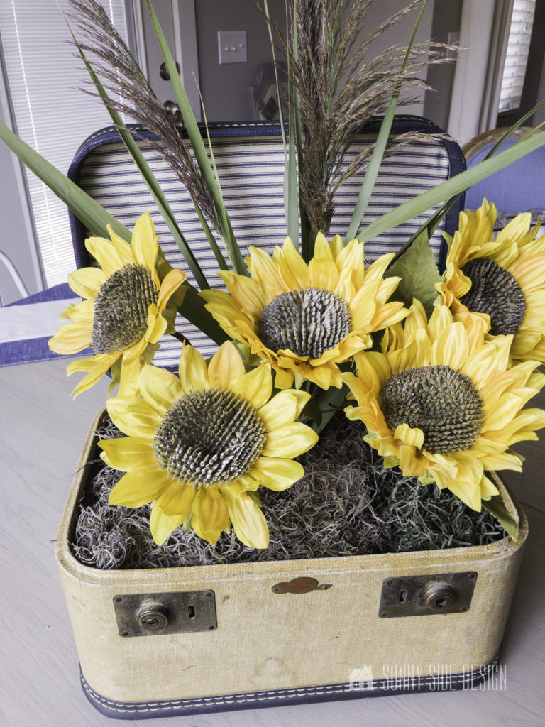 A clump of wild grasses is placed in the rear of the vintage case for this simple sunflower arrangement.