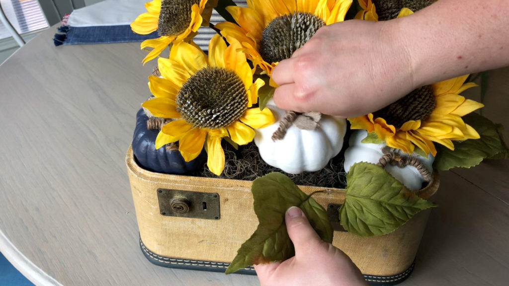 Place a few of the sunflower leaves under a few pumpkins for our sunflower arrangement.