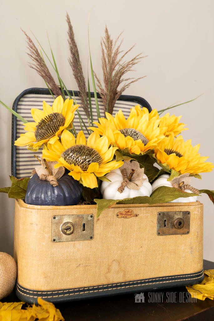 A vintage cosmetic case is used to make a simple sunflower arrangement. Case is filled with wild grassed, 5 large sunflowers along with white an navy blue pumpkins.