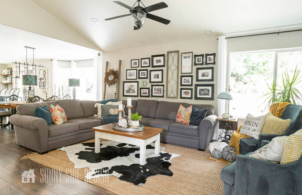 Living room featuring Cheap Fall decor ideas. Gray secional with fall inspired pillows. A cow rug is layered over the sisal rug, coffee table is styled with a galvanized tray, candles, knit pumpkins, acorns, plant and bead garland.