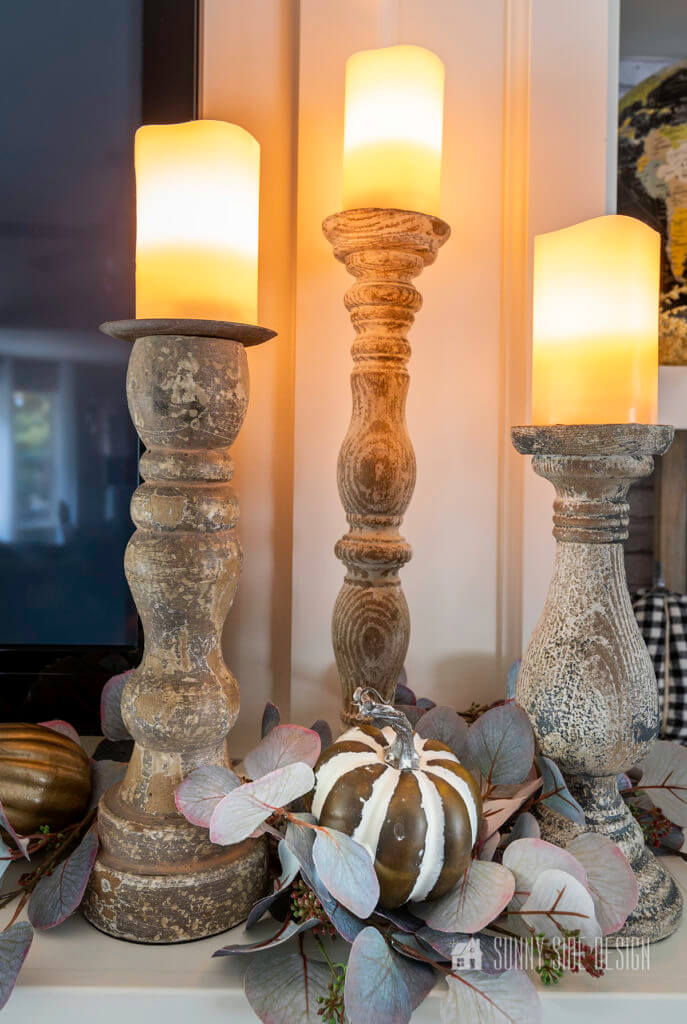 3 Glowing candles placed on the mantle with eucalyptus and pumpkins.