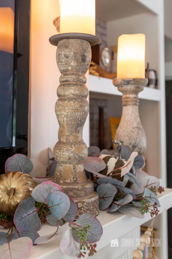 Cheap Fall Decor, 3 candlesticks on the fireplace mantle surrounded by faux eucalyptus and pumpkins.