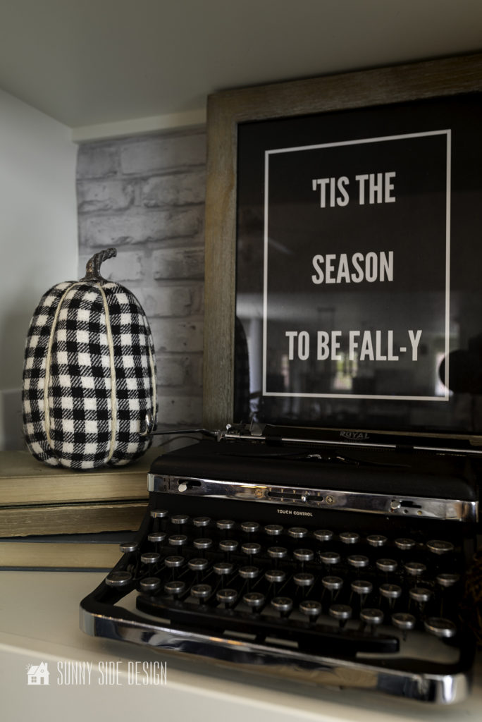 """Add cheap fall decor with FREE printable. Vintage typewriter on shelf with a buffalo plaid pumpkin on a stack of books and a framed printable """"'Tis the season to be fall-y"""""""