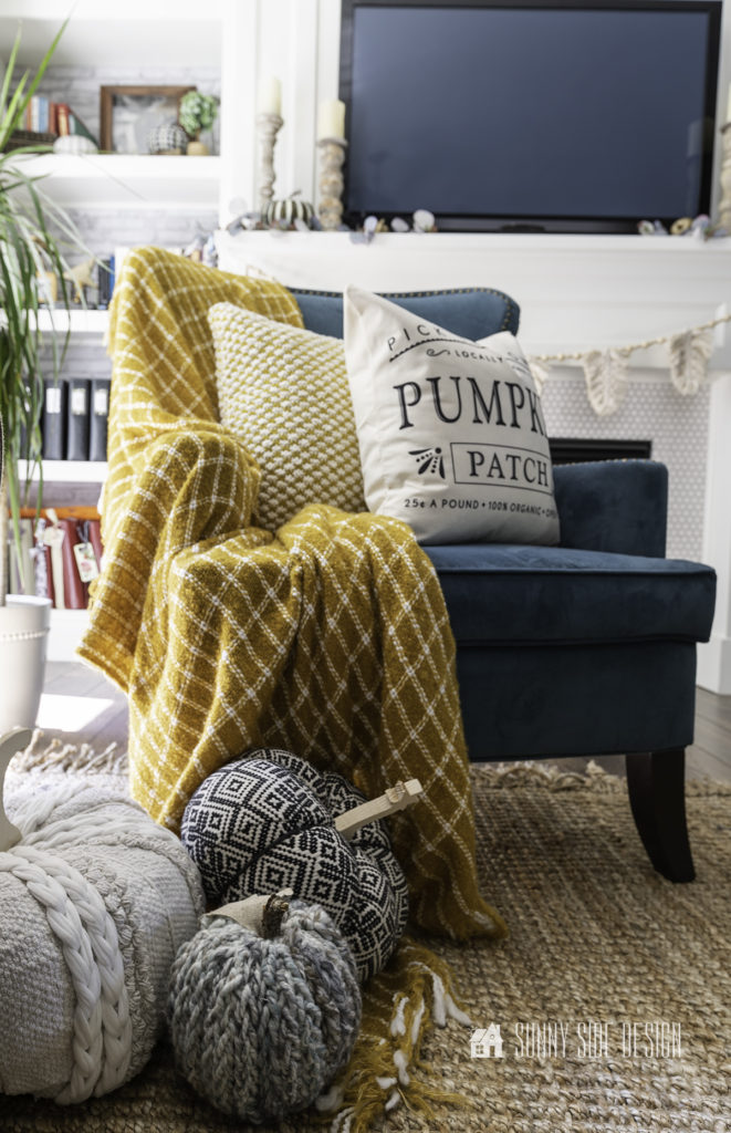 Peacock blue wingback chair with a mustard throw blanket and fall pillows. At the leg of the chair are 3 fabric pumpkins restng on the throw.