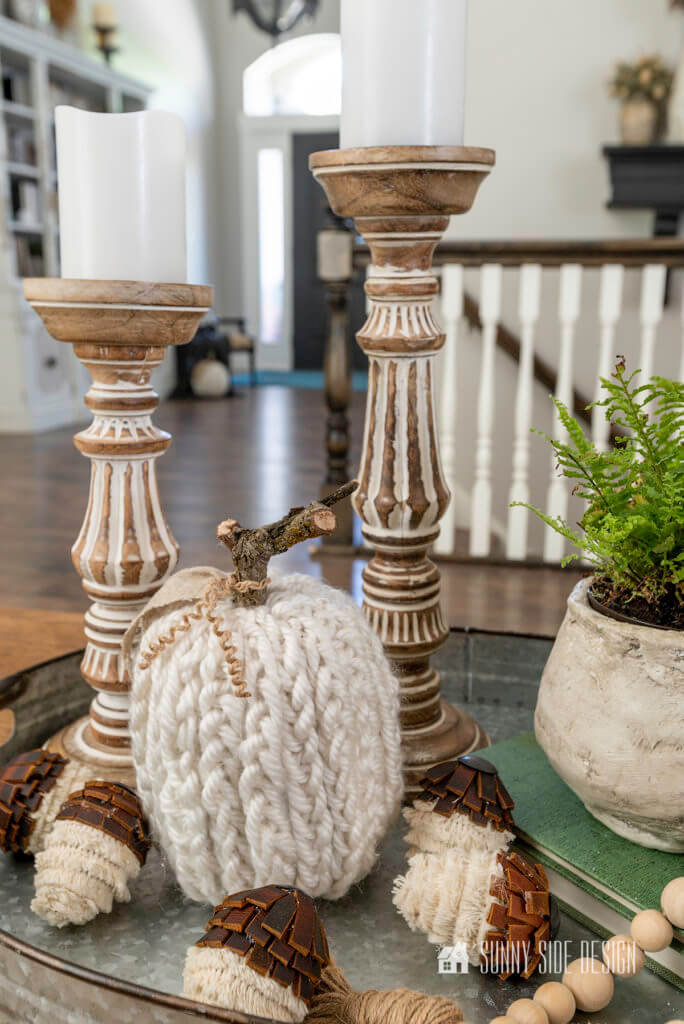 Cheap Fall Decor, Coffee table styled with a galvanized tray filled with 2 candlesticks, knit pumpkin, DIY Boho acorns and a plant stacked on a book with a bead garland