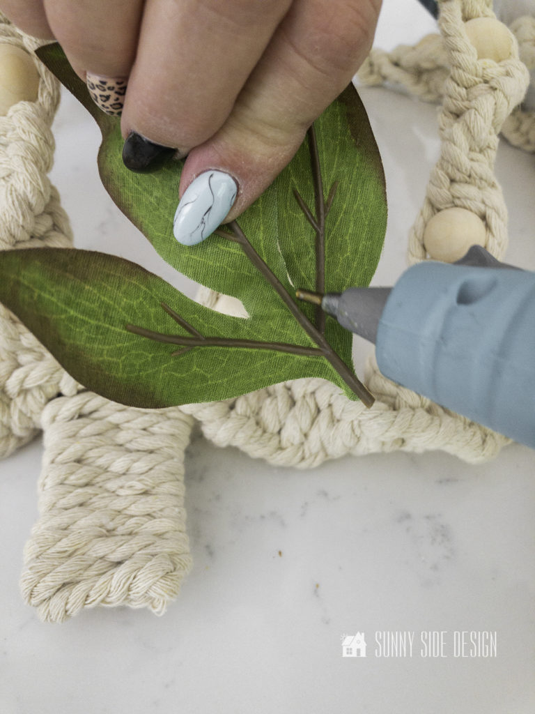 woman's hand applying glue to the back of a leaf.