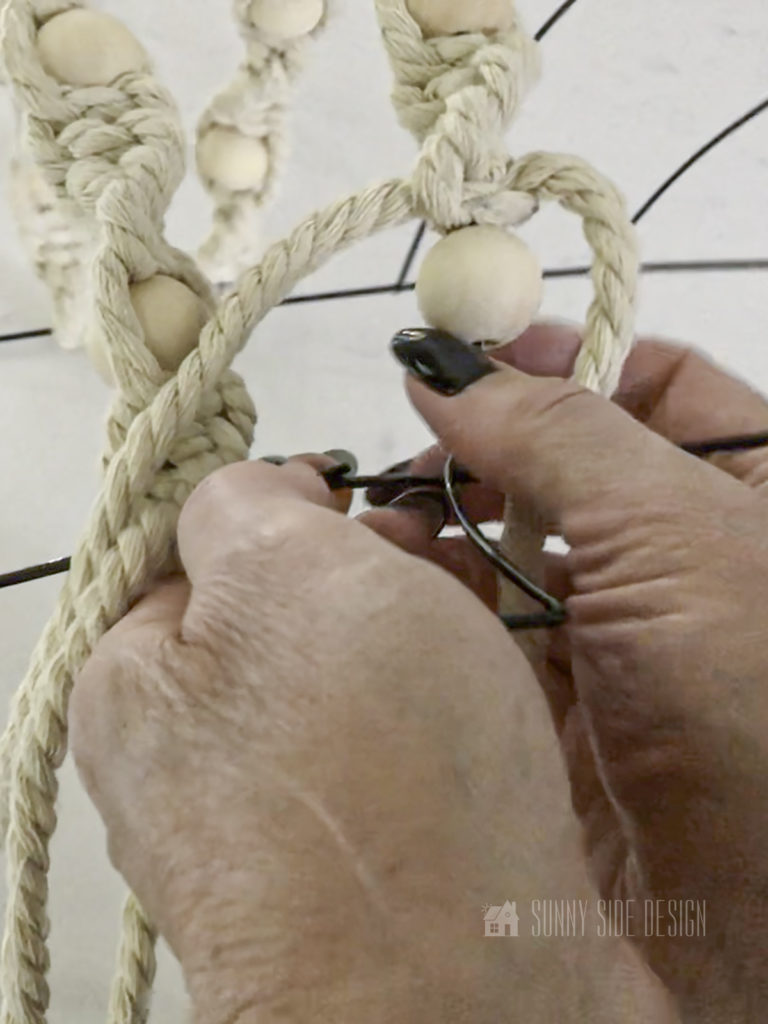 Woman's forming knot on DIY Fall Macrame Wreath.