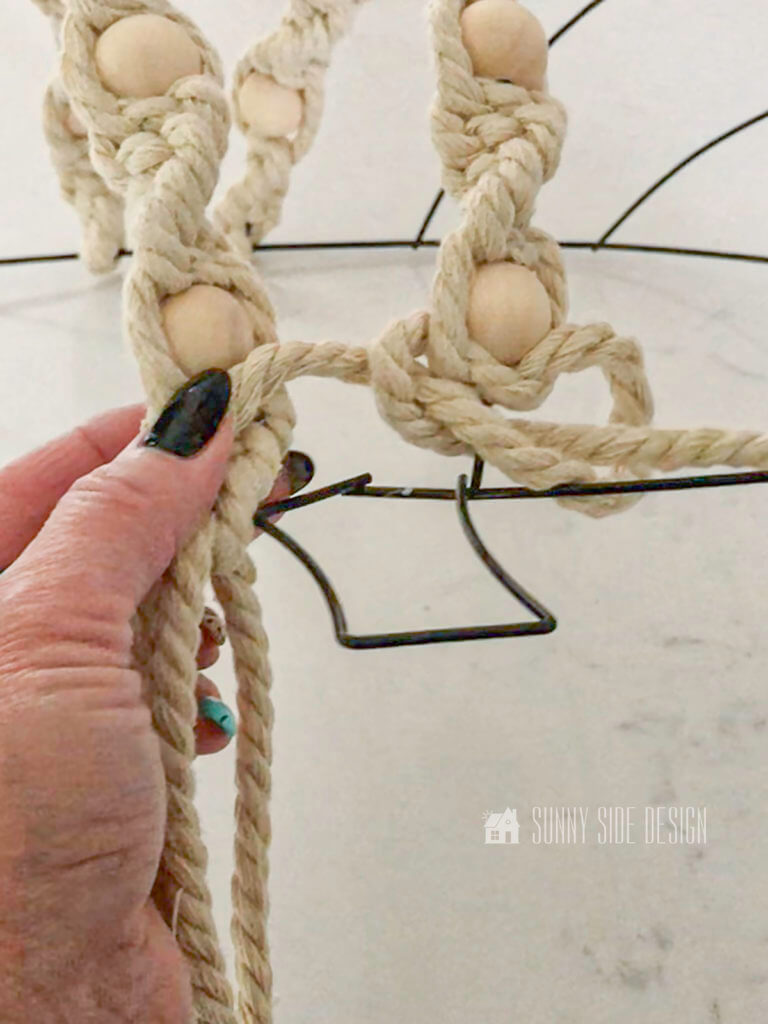 Woman's hand forming spiral knots on DIY Fall Macrame Wreath