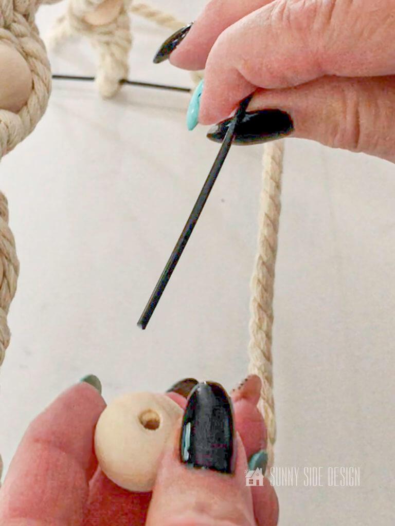 woman's hand threading bead onto pumpkin wire wreath frame.
