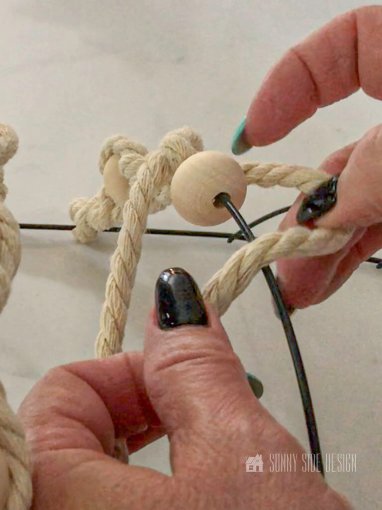 woman's hand forming macrame cord for spiral knot around bead.