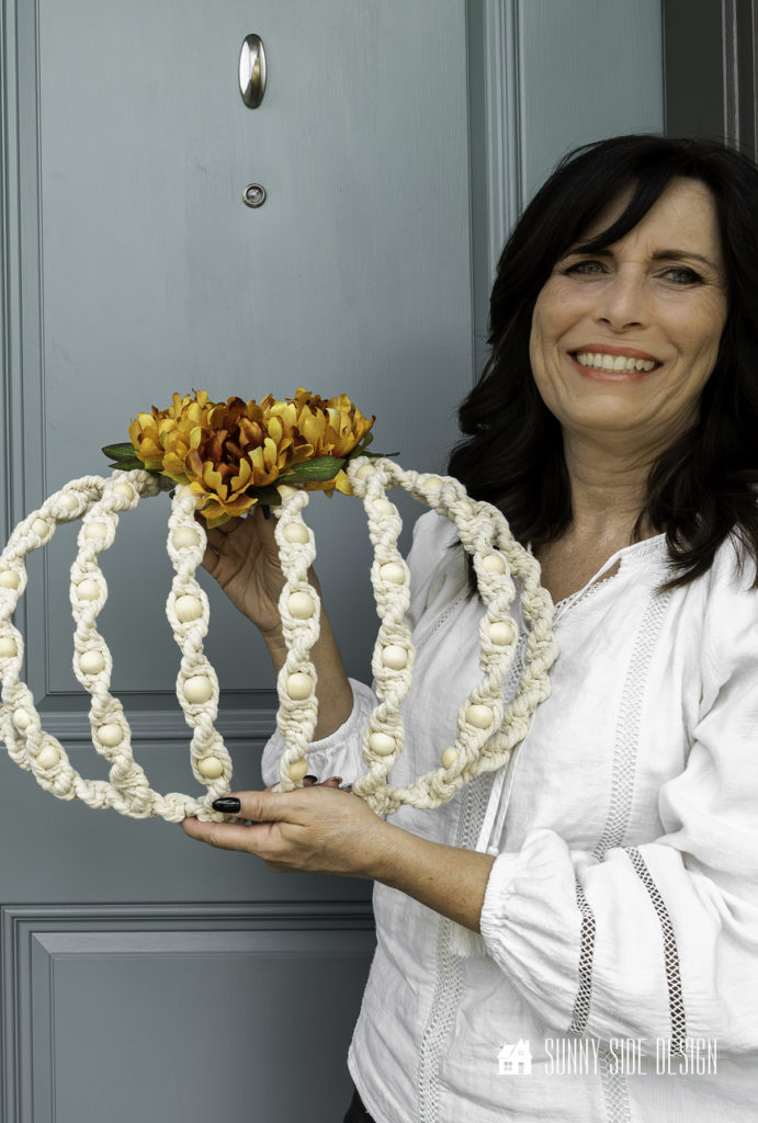 Woman holding DIY Fall Macrame Wreath in front of dusty blue front door.