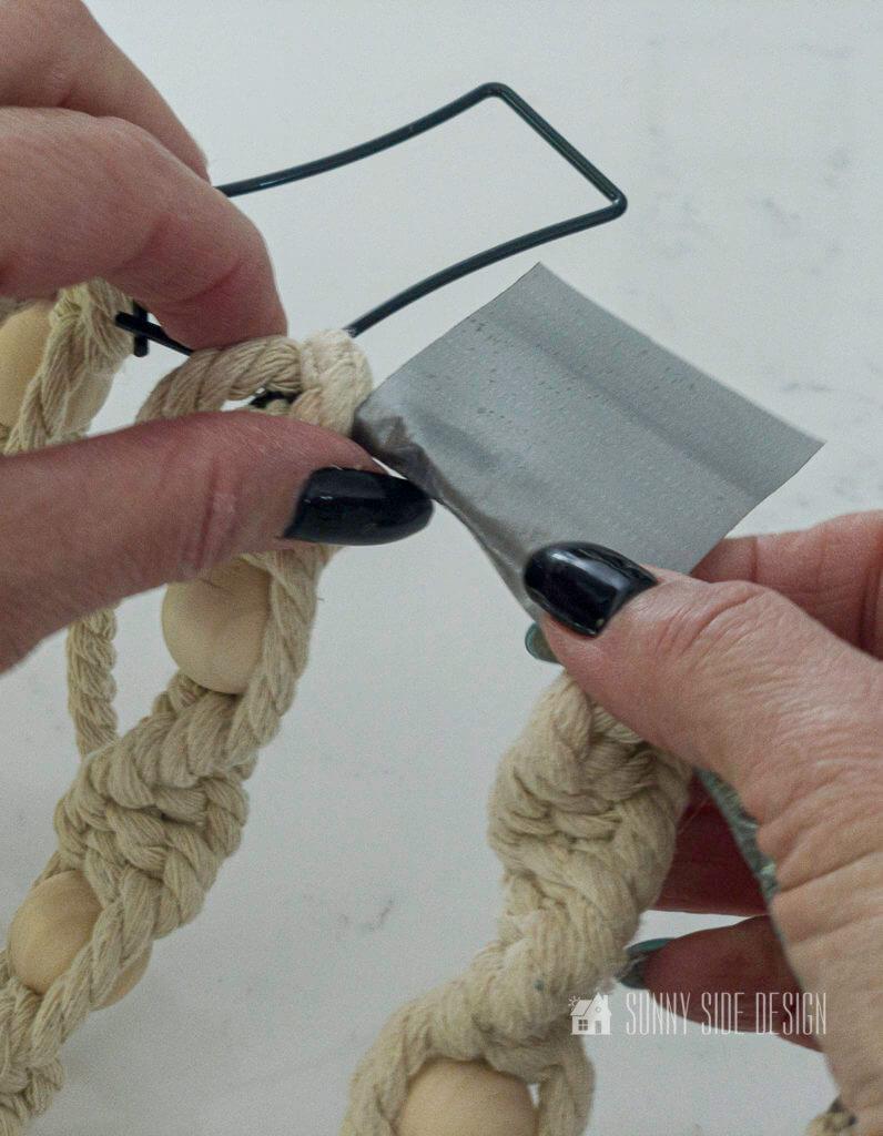 Woman's hand wrapping tape around cut macrame cord. DIY Fall Macrame wreath