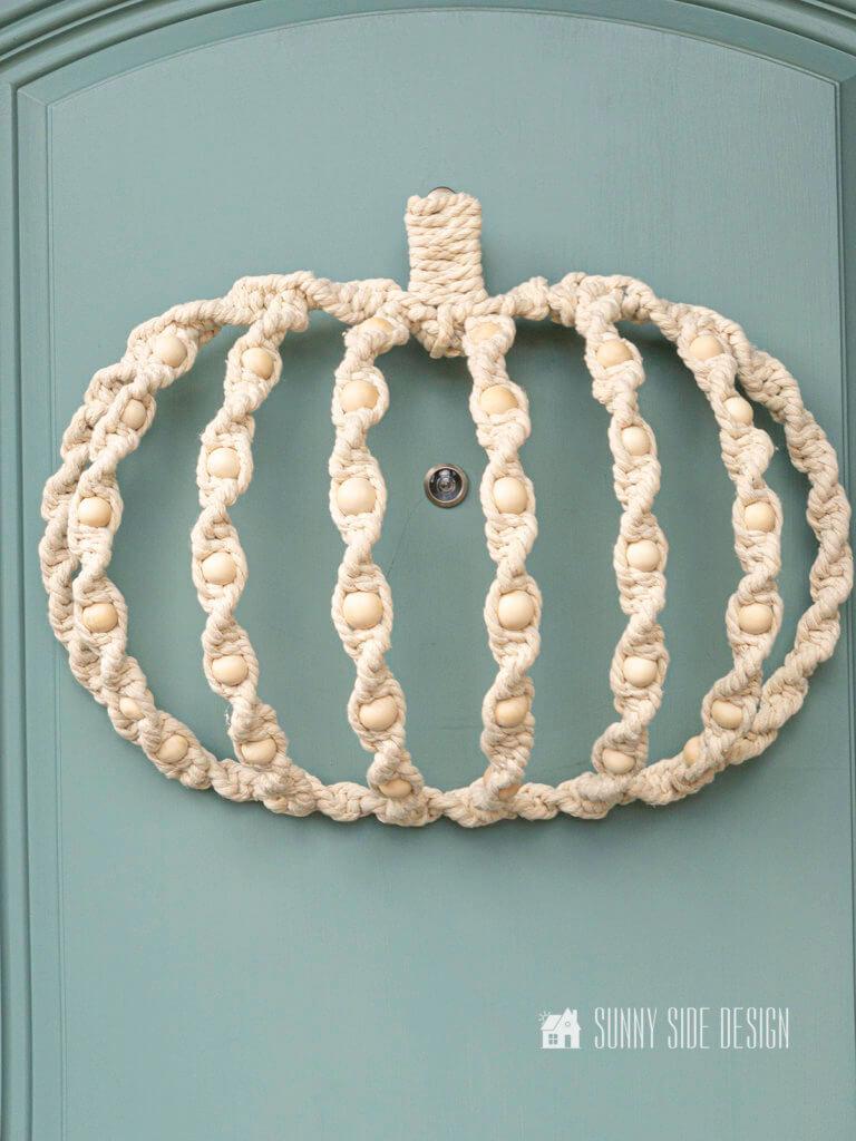 Completed DIY Fall Macrame Wreath, DIY Fall Macrame Wreath hung on dusty blue front door.