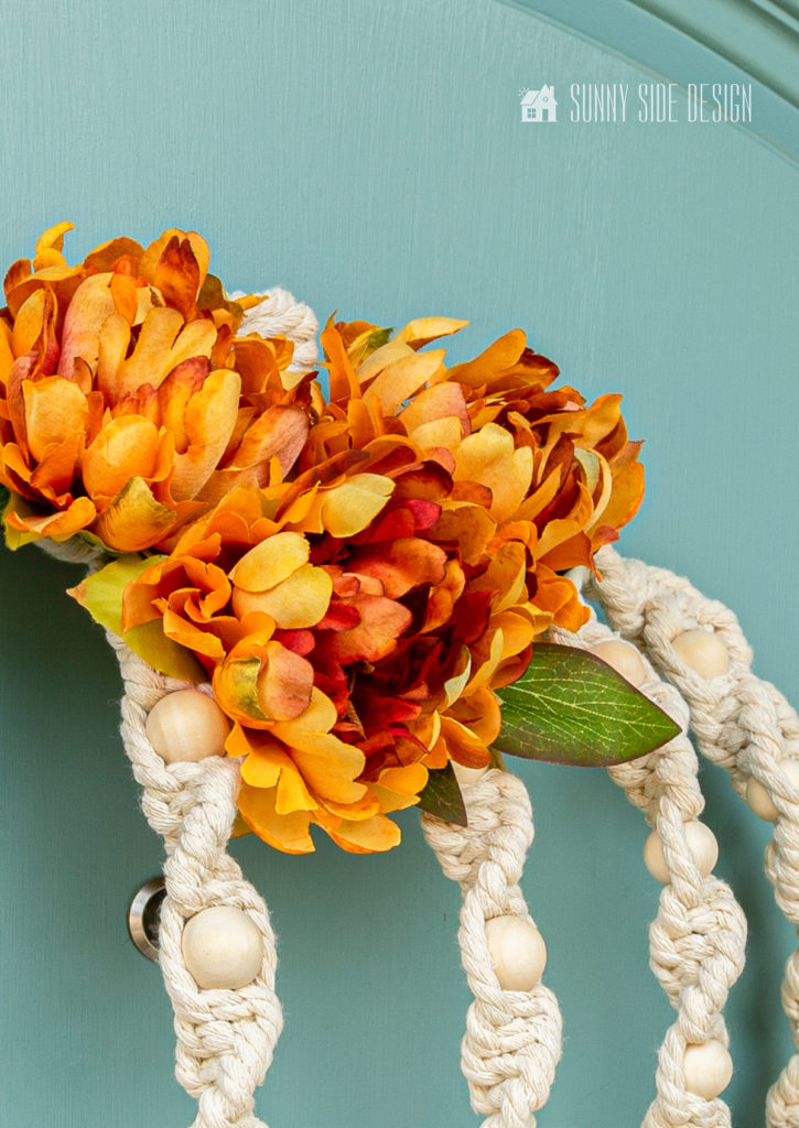 DIY Fall Macrame Wreath hung on dusty blue front door.