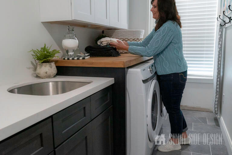 Woman with a blue sweater and jeans in laundry room sitting on newly built wood folding table. White front loading laundry appliances, white and black shaker cabinets.